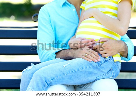 Young pregnant woman with husband sitting on bench in park - stock photo