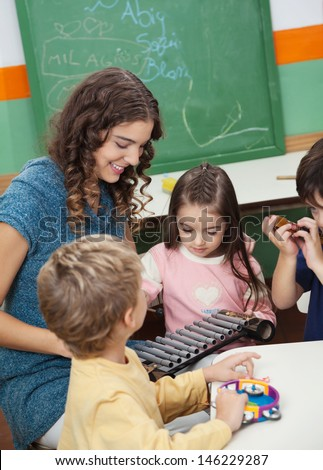 Young preschool teacher and children playing with xylophone in music class - stock photo