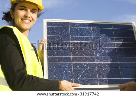 Young presenting a solar panel - stock photo