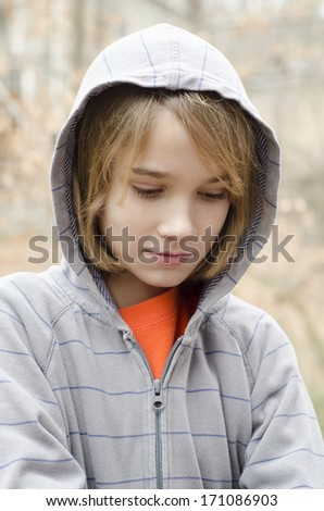 young preteen wearing a hoodie and looking down at the ground - stock photo