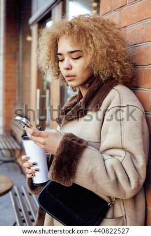 young pretty african american women drinking coffee outside in cafe, modern business woman lifestyle concept - stock photo