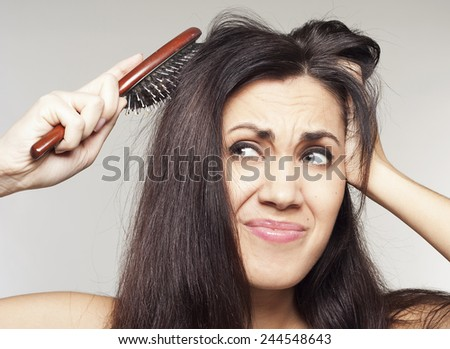 Young pretty angry woman with hairbrush - stock photo