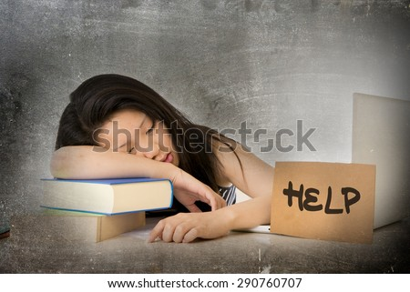 young pretty Asian Chinese woman student asleep on her laptop studying overworked with help sign leaning tired and overwhelmed on textbooks in stress eduction concept in grunge dirty background - stock photo