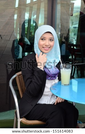 young pretty Asian muslim business woman in head scarf at cafe - stock photo