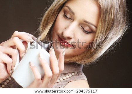 young pretty blond woman drinking coffee over beige background - stock photo