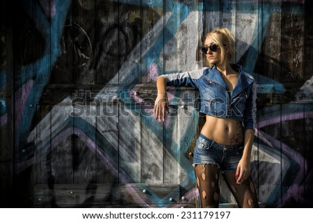 Young Pretty Blond Woman in Trendy Denim Fashion with Shades Leaning on Wooden Wall with Abstract Design. - stock photo