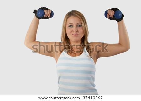 Young pretty blond woman in workout attire facing forward while holding and lifting two three pound weights with a funny facial expression - stock photo
