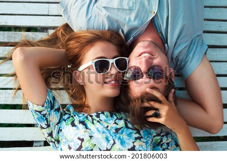 Young pretty blonde girl and her handsome boyfriend laying outdoor in white chubby chic wooden floor, hugs and enjoy the sun and romantic time together. - stock photo