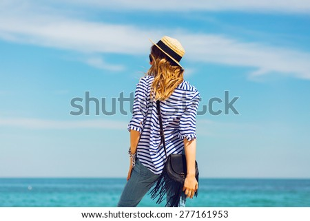 Young pretty blonde tanned   woman standing on the beach near the sea back waiting and dreaming about. Wearing straw hat and striped shirt. - stock photo