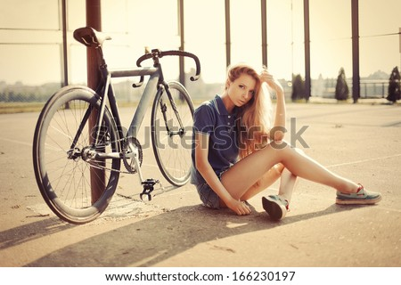 Young pretty blonde woman posing on the street with sport fixed gear bike in summer sunshine. Fashion portrait. - stock photo