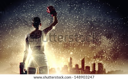 Young pretty boxer woman standing against city background - stock photo