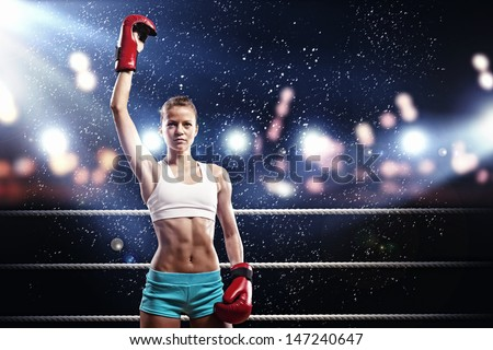 Young pretty boxer woman standing on ring under water drops - stock photo