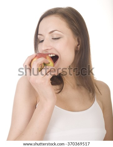 young pretty brunette girl eating red apple isolated on white - stock photo