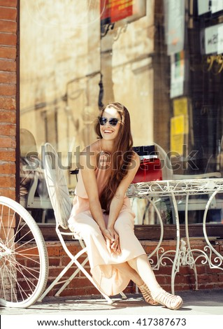 young pretty brunette woman after shopping sitting at cafe outside on street smiling - stock photo