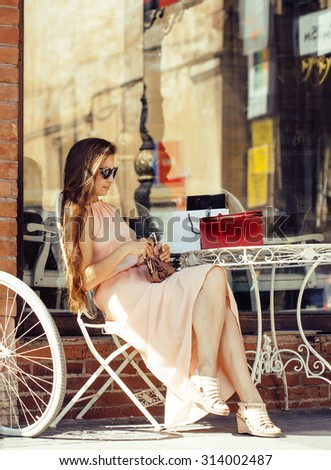 young pretty brunette woman after shopping sitting at cafe outside on street smiling, wearing dress and sunglasses, summer time - stock photo
