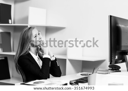 Young pretty business woman sitting at the desk with computer in blue office - stock photo