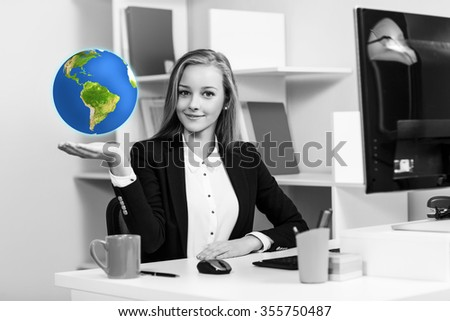 Young pretty business woman sitting at the desk with earth on hand in blue office. Elements of this image furnished by NASA - stock photo