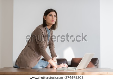 Young pretty business woman working with laptop in the office looking away pensive - stock photo