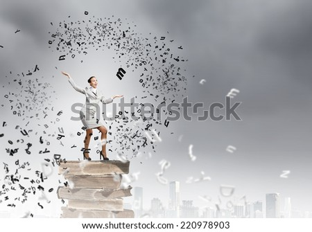 Young pretty businesswoman juggling with black characters - stock photo
