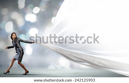Young pretty businesswoman pulling white blank banner - stock photo