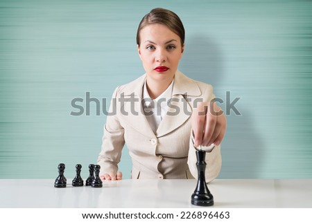 Young pretty businesswoman sitting at table and playing chess - stock photo