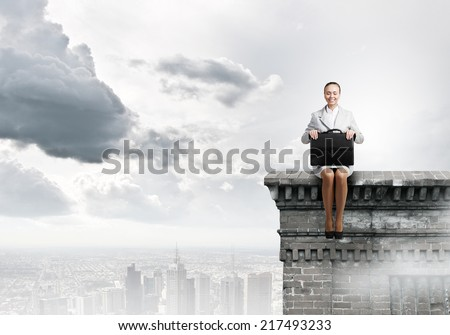 Young pretty businesswoman sitting on top of building high above city - stock photo