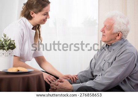 Young pretty carer and her older nice male ward - stock photo