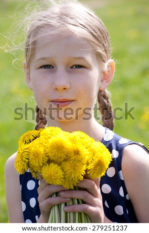 young pretty caucasian girl standing with yellow dandelions in hands, face closeup - stock photo