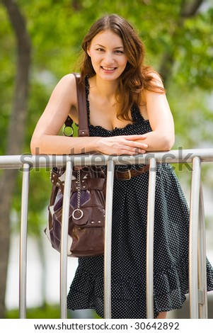 young pretty caucasian lady outdoor with handbag - stock photo
