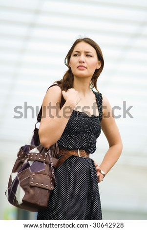 young pretty caucasian lady outdoor with handbag getting impatient - stock photo