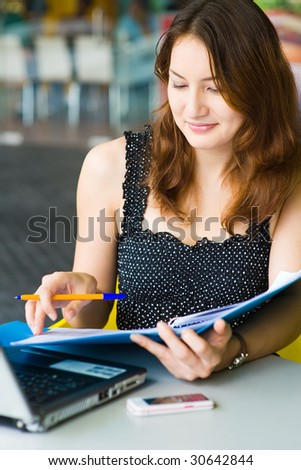 young pretty caucasian lady using laptop outdoors - stock photo