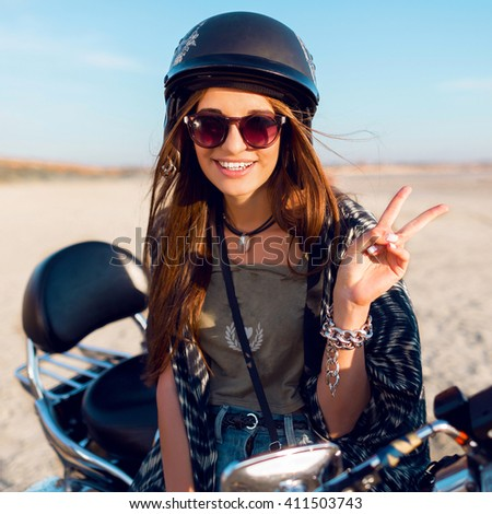 Young pretty cheerful woman sitting on motorbike on the beach and show signs, wearing stylish crop top , shirts, have perfect fit slim tamed body and long hairs. Outdoor lifestyle portrait. - stock photo