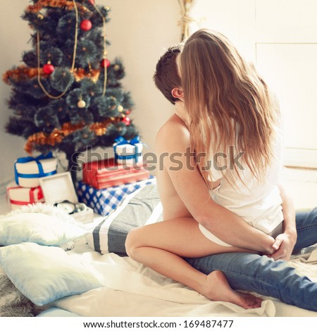 Young pretty couple celebrating christmas together at home near christmas tree with gifts presents love each other and kissing  - stock photo