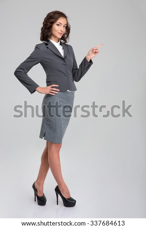 Young pretty curly happy smiling woman in formalwear and heel shoes pointing away on copyspace - stock photo