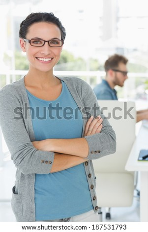 Young pretty designer smiling at camera in creative office - stock photo
