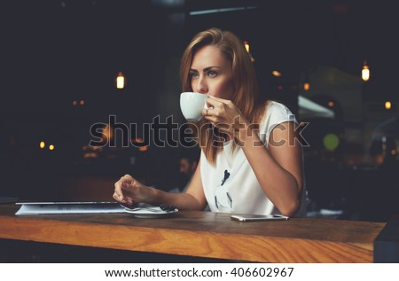 Young pretty European woman drinking cappuccino while relaxing in modern cafe bar after work day, dreamy female enjoying cup of tea while sitting in cozy coffee shop during her recreation time  - stock photo