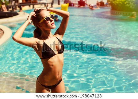 Young pretty fashion sport woman posing outdoor in summer on tropic island in hot weather in bikini on pool party - stock photo