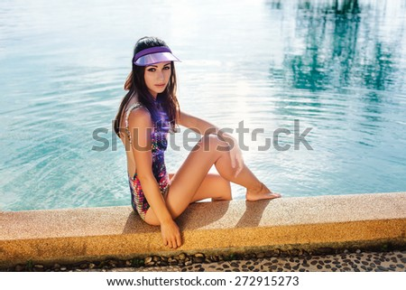 Young pretty fashion sport woman posing outdoor in summer on tropic island in hot weather in bikini on pool party. Outdoors lifestyle portrait - stock photo