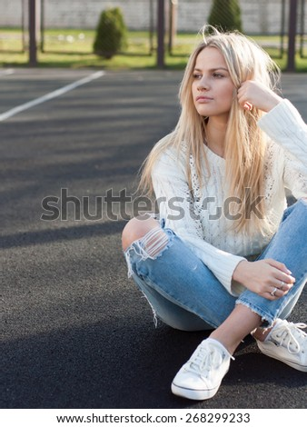 Young pretty fashionable blonde woman dressed in ripped jeans and white sweater sitting on the ground in summer and having fun - stock photo