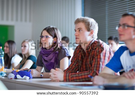 young, pretty female college student sitting in a classroom full of students during class - stock photo