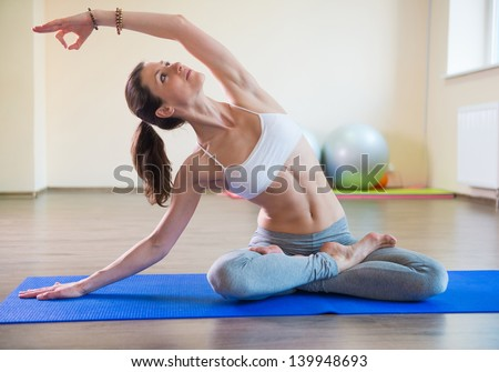Young pretty female exercising in fitness club - stock photo
