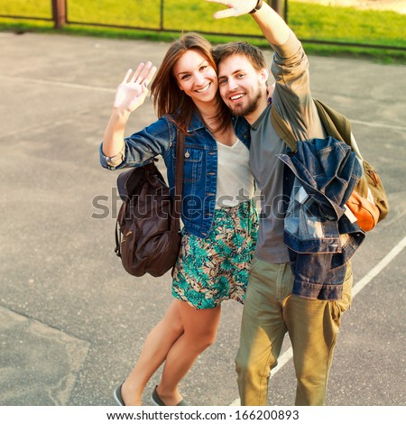 Young pretty funny happy smiling couple posing outdoor on school yard and saying hello and having fun together in love - stock photo