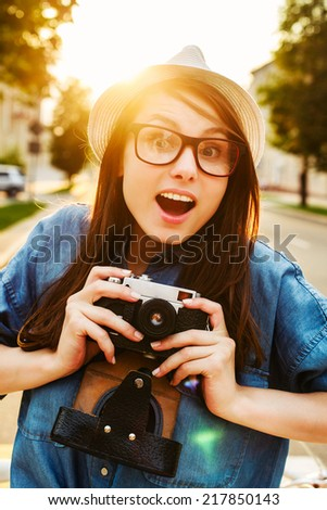 Young pretty funny sensual woman photographer tourist girl posing outdoor in evening with vintage photo camera smiling and surprised in hat and hipster style glasses  - stock photo