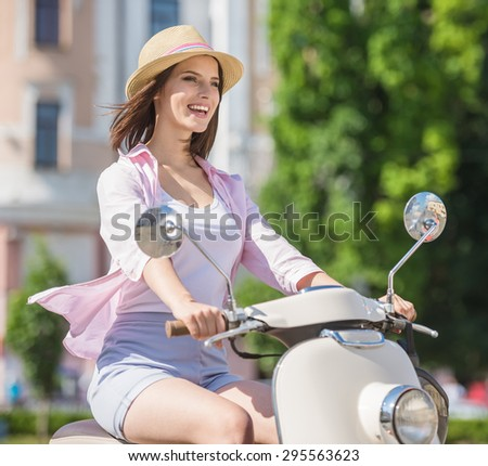 Young pretty girl driving scooter in european city. Side view. - stock photo