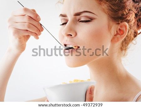 Young pretty girl eating corn flakes - stock photo