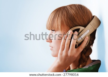 Young pretty girl  head with big headphones - stock photo