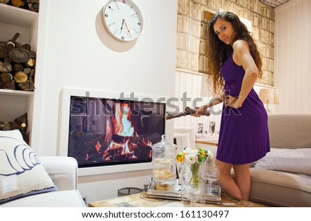 young pretty girl ignites fireplace in the house. Interior dutch design, living room - stock photo