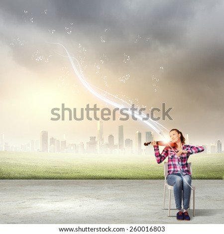 Young pretty girl in casual playing violin - stock photo