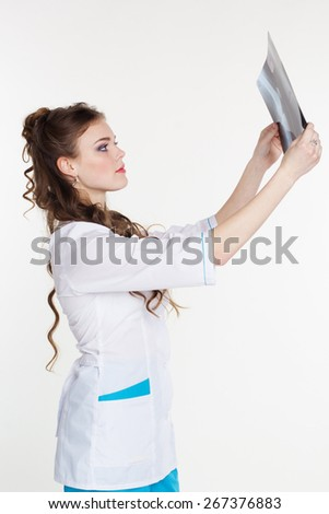 Young pretty girl intern looking at the x-ray picture of knee in hospital - stock photo