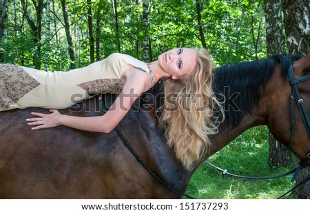 Young pretty girl laying on horseback in the forest - stock photo